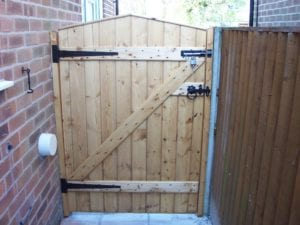 back of a wooden gate with black hinges and padlock