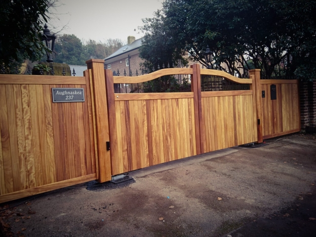 Iroko chester design with metal spindles driveway gates in osmo oil